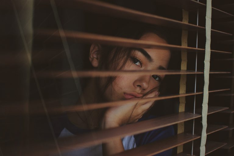 A obessed girl looking out of the window